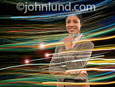 A smiling woman business executive is surrounded by streaming data in the form of speeding colored lights in a stock photo about connections, future technology, and online communications.