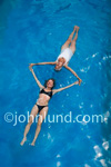 Mother and daughter relaxing in a swimming pool of cool blue water.  Mother is wearing a white one piece swim suit and her daughter is wearing a two piece black bikini suit. Women in a swimming pool pic.