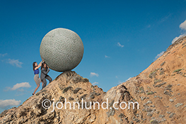 Two women push a giant sphere of money over a rocky peak just to have another steeper climb ahead in a stock photo about women's finances, investing, savings and money challenges.