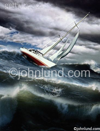 Picture of a sailboat in a violent storm with wind blown white-capped waves tossing in a stormy sea beneath the dark storm clouds of a squall.