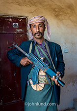 A Yemeni man cradles his AK-47 sub machine gun as he poses for his portrait at a military checkpoint on the outskirts of Saana, Yemen.