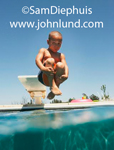 A young pre-teen boy is tucked into a cannon ball and in mid air just before he hits the water in the pool. Very close cropped hair.  Bright sunny day with a clear blue sky as the background.