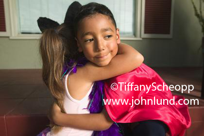 Young black boy hugging a young white girl.  The boy has kind of an embarassed look on his face. Cute adorable kids hugging pics for advertising.