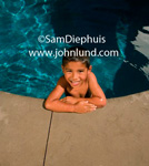 Picture of a young Hispanic or Latino boy is at the edge of the pool with his arms crossed in front of him and resting on the cement edge of the swimming pool. The boy is smiling happy and having fun in the water.