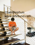 Image of a young boy sitting on the stairs at home playing a video game or working on his ipad.