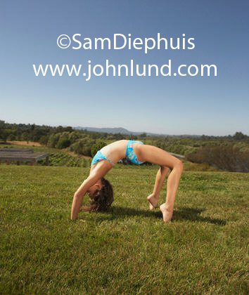 Young white girl in a two piece bathing suit doing acrobatic stunts on the grass. The girl is bent over backwards with her back towards the ground. Blue sky above.