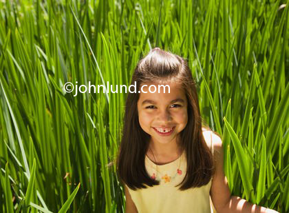 Stock photo of a young hispanic or Mexican girl standing in tall grass... taller than she is. The cute smiling young mexican girl is looking at the camera which is above her. Long brown hair and pretty yellow blouse. Pictures of happy kids.