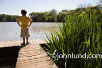 Picture of a young white child, a boy, standing on a dock with his hands on his hips and his back to the camera.  The kid is wearing a yellow shirt and kahki shorts.  Photos of a kid alone on a dock looking out at the river or lake.