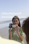Stock photo of a young woman taking a video at the beach with her camcoder. She is smiling and facing the camera with the beach and the ocean visible in the background.