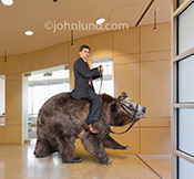Surviving a bear market is just one concept illustrated by this humorous image of a businessman riding a bear in a corporate lobby.