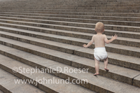 A toddler in diapers climbs a vast set of steps in this photo illustrating concepts including the future, possibilities and growth.