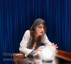 A Gypsy fortune teller looks up from her  crystal ball with a worried expression in a stock photo about forecasting the future.