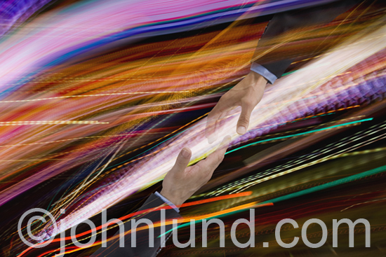 Two hands come together in a handshake amid the speed and chaos of streaming data in the form of colorful light trails.