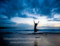 Picture of a teen aged girl jumping for joy on a tropical beach after sunset. The sky is filled with dramatic clouds and her image is reflected in the wet sand.