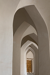 A series of white columns form an abstract corridor leading to an ancient door in a stock photo about choice, journeys, and possibility.