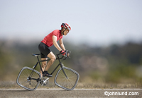 A cyclist strains as he attempts to ride a bicycle with square tires in a business, concept and lifestyle stock photo. Funny picture of a cyclist riding a bike with square tires. He has on a red shirt and dark shorts. He is wearing a safety helmet.