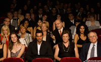 A man is in the audience in a theater during a performance and is rudely using his cell phone during the show.  Bad manners, inconsiderateness, and poor social skills or just unaware.