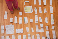 A woman's feet are seen surrounded by piles of receipts as she budgets and plans for her expenses and taxes