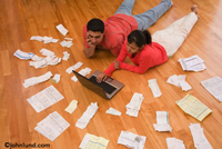 An Hispanic couple lays on their living room floor with thier receipts spread out and use a laptop to manage their finances. Picture of people paying bills.