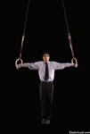 Picture of a business man gymnast, arms outstretched to each side and parallel to the ground, holding onto and suspended by a pair of gymnastic rings.