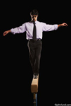 Photo of a business man on the balance beam in a metaphor for the challenges facing small business across the world. The man has his arms stretched out at shoulder level, one foot in front of the other, and balancing carefully.