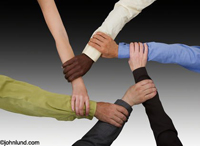 In a symbol of teamwork six hands from differing racial heritages form a circle by grasping each others wrists. All but one of the arms has sleeves. One bare arm.