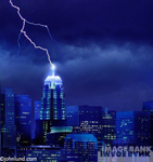 Skyscraper being struck by a huge lightning bolt. A dark stormy night during an electrical storm is lit up when a bolt of lightning strikes the top of a tall building in the city.