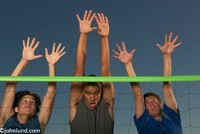 Men playing volleyball, three men raise their hands up over the net as they jump to block a shot. Blocking a shot in a beach volleyball game. Teamwork in action.