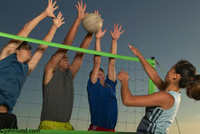 Woman spiking the volleyball into a block by opposing players. The woman who spiked the ball still has her hand at the top of the net. The opposing players are all up in the air arms and hands up high.