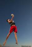 A male volleyball player is leaping high into the air to serve the ball. The man is wearing bright red shorts and a blue top.  A clear blue sky is the backdrop for this sports related image.