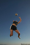 Photos of a woman playing beach volleyball and serving from high in the air. The female player is wearing black shorts with white stripe along the sides and a black tank top. The ball is poised above her head.