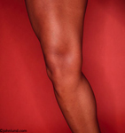 Photos of a woman body builder's well-muscled leg photographed against a red wall with a ring flash.