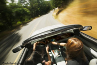 Photos of two women riding in a convertible as it speeds down a tree lined road. The top is down on the car and the road and surroundings are blurred from the speed.