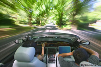Photos of a couple speeding down a country road in a silver Jaguar convertible with the top down. Trees and shrubbery are just a blur as the car speeds down the road. Male passenger is working on his computer.