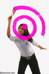 An attractive ethnic woman painting a target bulls eye in bright pink paint on a glass surface. She is defining her goals.