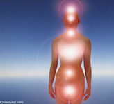 Chakras including the crown Chakra and the root chakra as glows of light on an Asian woman's body.