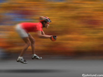 Unusual funny photo of an African American woman racing on an invisible bicycle, an indication of lacking the proper equipment and resources to succeed.