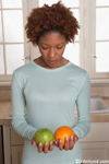 Picture of a woman comparing an apple and an orange. She is holding a green apple in one hand and an orange in the other. She is wearing a light blue blouse and the picture is from the waist up.