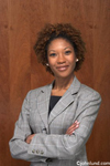 Portrait of an African American woman corporate executive. Successful lack businesswoman with confidence and attractive too.  She is wearing a gray business suit and she is smiling at the camera.