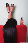 An ethnic woman sits facing away from us with her long black hair over the chair as she uses her cell phone. Lifestyle and leisure photos.