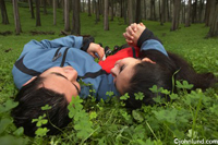 An Hispanic man and woman lay in the grass together near the woods. He is wearing a blue coat and she is wearing a red one. Behind them in the background you can see the trees of the forest.