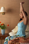 Picture of an Asian woman sitting on the edge of the bed in her pajamas and stretching before getting up in the morning. She is in a motel room. She has on a blue night gown.  There are flowers next to her bed.