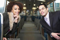 An African American woman and a Chinese American man seated on a Rapid Transit Car look happily towards the viewer. She is in a fur lined coat and he is in a smart looking suit.