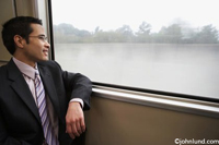 A Chinese American Businessman sits in a commuter train and watches the scenery fly by as he travels to work in comfort. The man is wearing a business suit and leaning his arm on the window.