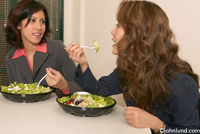 Two business woman are eating healthy salads in a business environment. The women are looking at each other and chatting about work or something else.