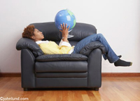 An African American woman relaxes in an overstuffed chair holding and examining a world globe symbolizing travel and adventure.