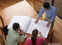 An Architect presents and explains his building plans and remodeling blueprints to clients in their upscale Living Room