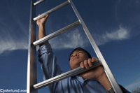 A man climbs up a ladder that disappears off into the sky. The man is reaching up to the next rung with his right hand while holding a lower rung with the other hand.