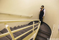 A businessman stands in contemplation, alone in the office stairwell with is coat slung over his shoulder. The stairwell and railings are white.