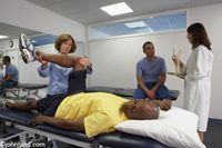 A woman physical therapists works with a patient while a lab technician confers with another patient in the background. The patient has a yellow shirt, blue pants, and his head is resting on a white pillow.
